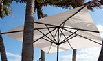 Sonnenschirm Primus von Caravita quadratisch in weiss am Strand